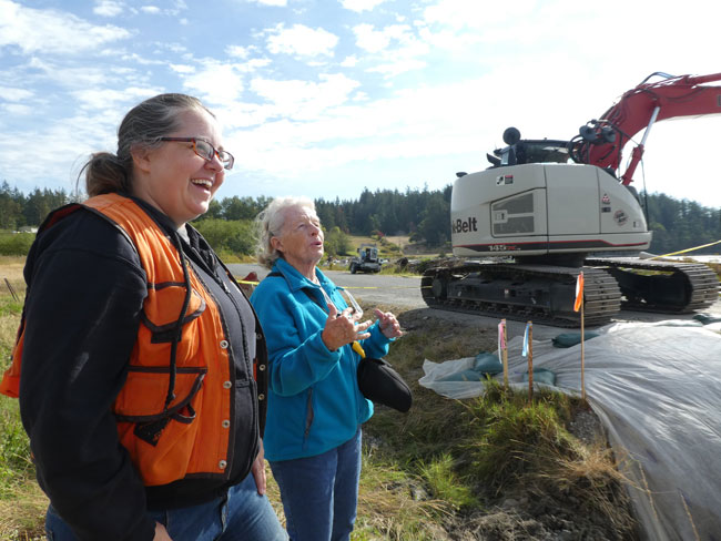 A Female conservation district employee is in the foreground smiling and laughing with an elderly woman with large machinery and work happening in an outdoor setting behind them.